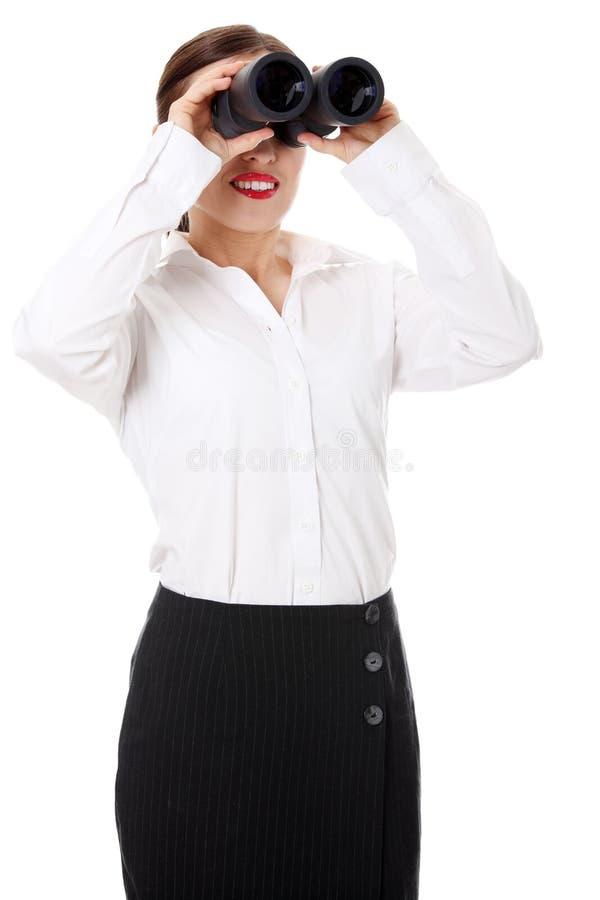 La donna di affari osserva il binocolo del threought fotografie stock libere da diritti