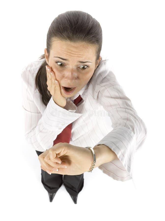 La donna di affari osserva in ritardo fotografie stock libere da diritti