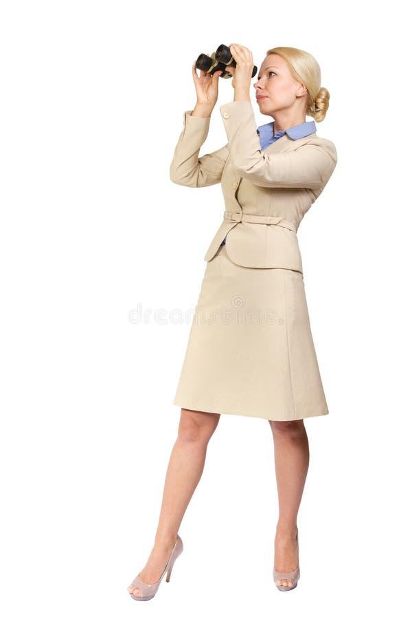 La donna di affari osserva tramite il binocolo fotografia stock