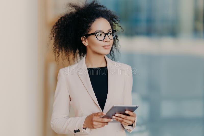 La donna di affari pelata scura elegante attraente utilizza la compressa digitale, vestita nell'usura convenzionale, supporti in  immagini stock libere da diritti