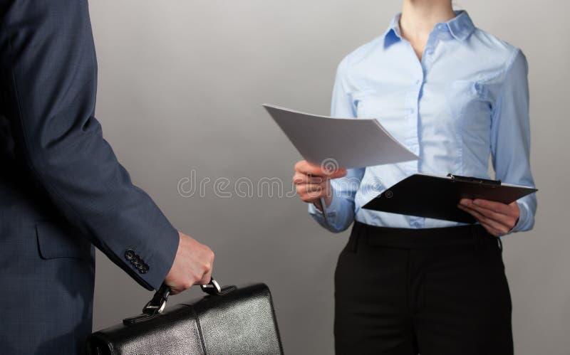La donna di affari raggiunge fuori i documenti ad un uomo d'affari con briefc immagini stock