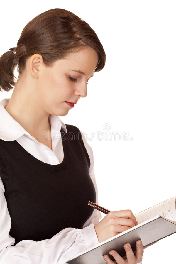 La donna di affari scrive in blocchetto per appunti immagine stock