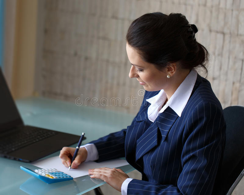 La donna di affari scrive in ufficio fotografie stock