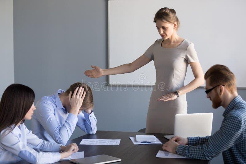 La donna di affari seria chiede all'impiegato guastato di lasciare la riunione fotografie stock libere da diritti