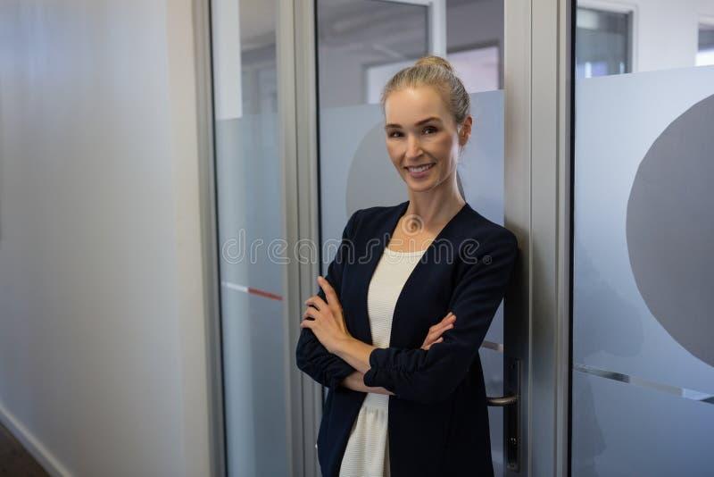 La donna di affari sorridente con le armi ha attraversato la porta facente una pausa all'ufficio fotografia stock libera da diritti