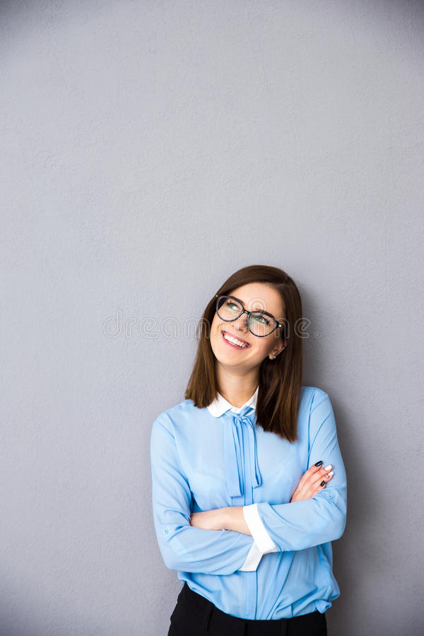 La donna di affari sorridente con le armi ha piegato cercare il copyspace fotografia stock libera da diritti