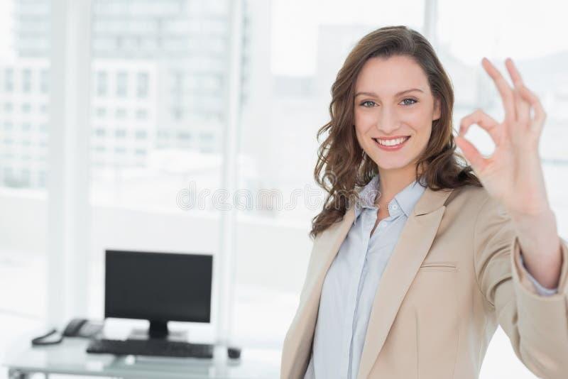 La donna di affari sorridente elegante che gesturing okay firma dentro l'ufficio fotografia stock
