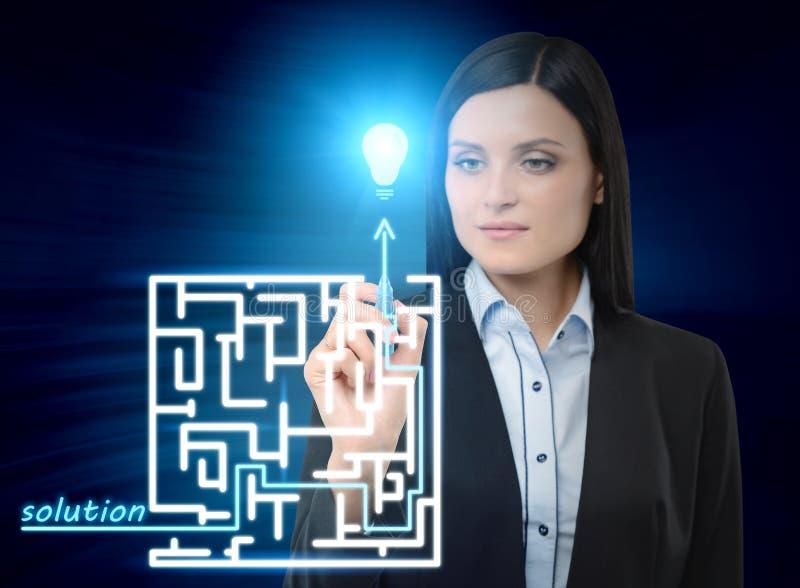 La donna di affari sta disegnando un labirinto con la soluzione sullo schermo di vetro Illusione moderna dell'ologramma immagini stock