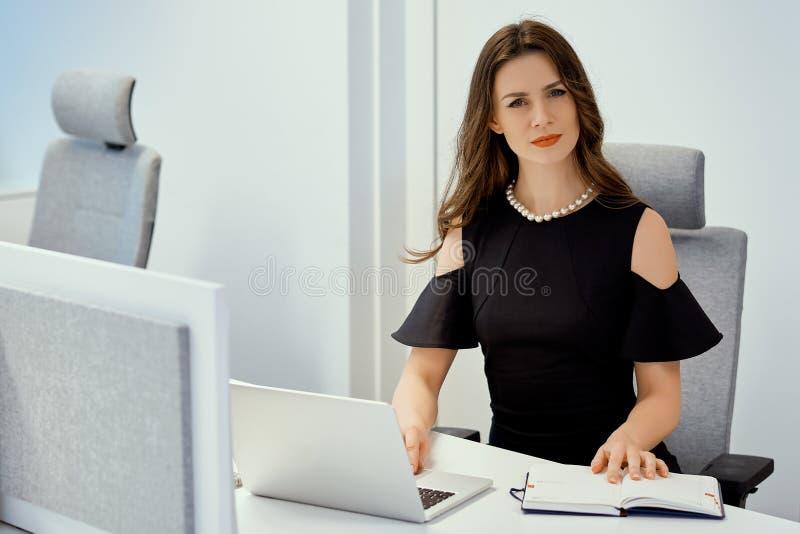 La donna di affari sta sedendosi allo scrittorio con il computer ed il calendario fotografie stock