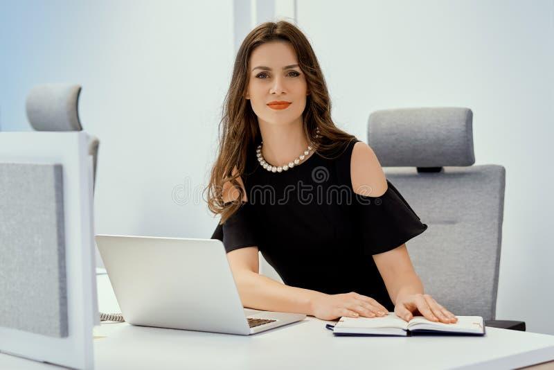 La donna di affari sta sedendosi allo scrittorio con il computer ed il calendario fotografia stock libera da diritti