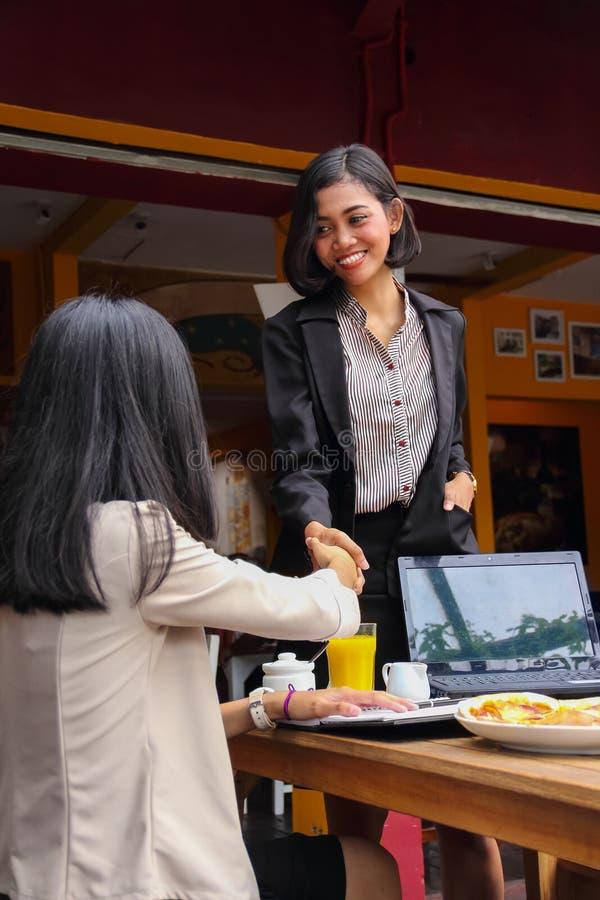 La donna di affari sta stringendo le mani mentre si incontra con la sua conoscenza di affari immagini stock