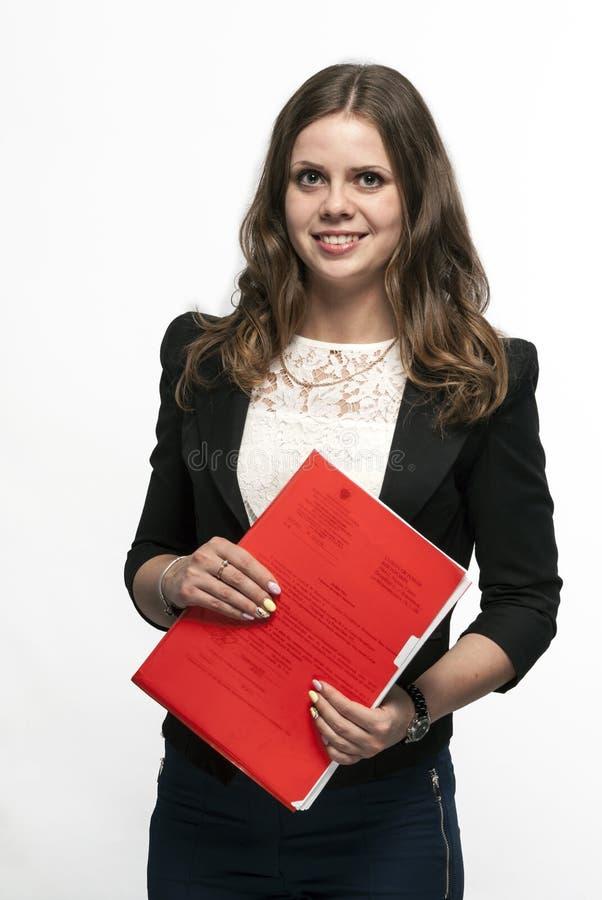 La donna di affari sta tenendo una cartella documenti rossa immagine stock libera da diritti