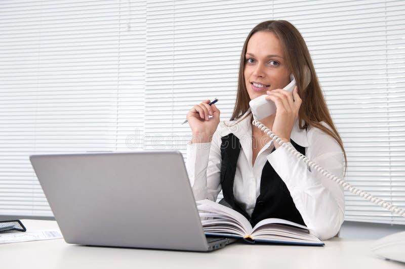 La donna di affari sul telefono esamina la macchina fotografica fotografia stock libera da diritti