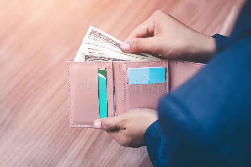 La donna di affari tiene i soldi nella tasca, nelle attività bancarie e nel concetto di risparmio fotografia stock