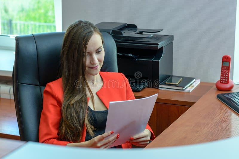 La donna di affari in vestito rosso si siede in una sedia di cuoio e nella lettura del contratto, controllante la carta fotografia stock libera da diritti