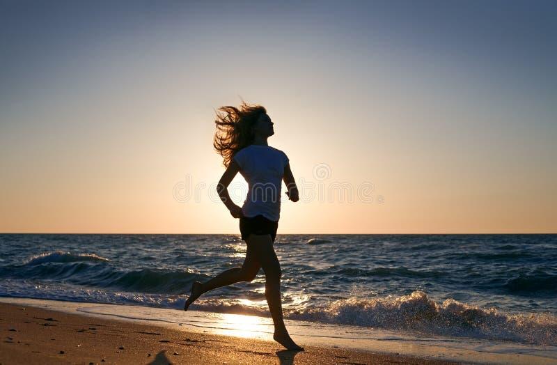 La donna di bellezza funziona sulla spiaggia del mare immagini stock libere da diritti