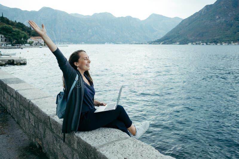 La donna di blogger in cardigan grigio e zaino blu scrive su un rivestimento fotografia stock