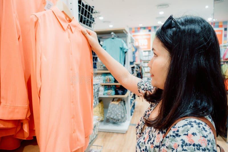 La donna di consumismo ? felicit? mentre comperano copre del grande magazzino, ritratto della giovane donna che sceglie i vestiti fotografie stock libere da diritti
