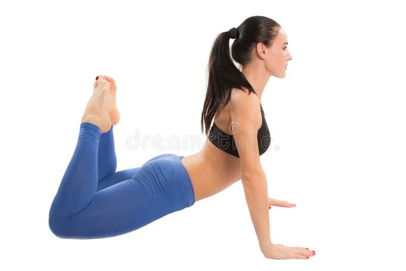 La donna di forma fisica fa l'allungamento sulla posa di yoga immagini stock