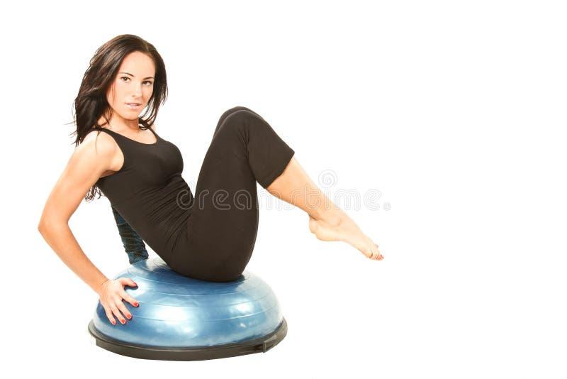 La donna di forma fisica fa la stirata sulla posa di yoga fotografia stock