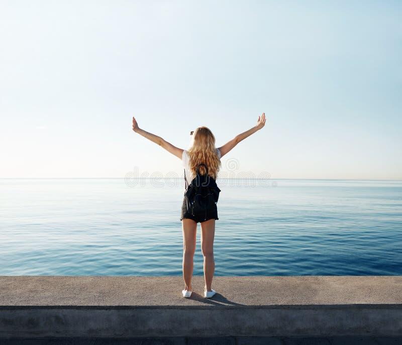La donna di libertà felice e libera a braccia aperte sulla spiaggia all'alba soleggiata immagine stock libera da diritti