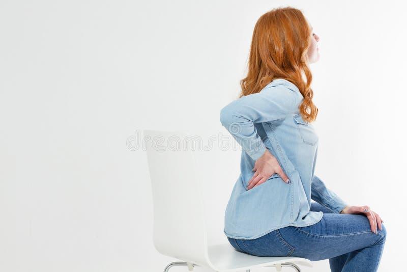La donna di mezza et? si siede su una sedia mentre tocca il suo spazio posteriore della copia immagini stock libere da diritti
