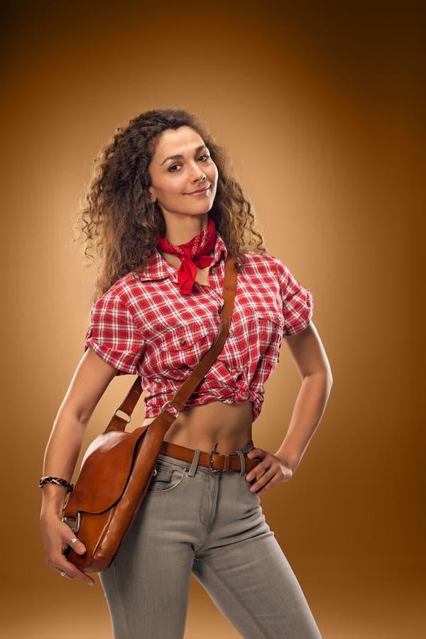 La donna di modo del cowgirl sopra un fondo marrone immagini stock