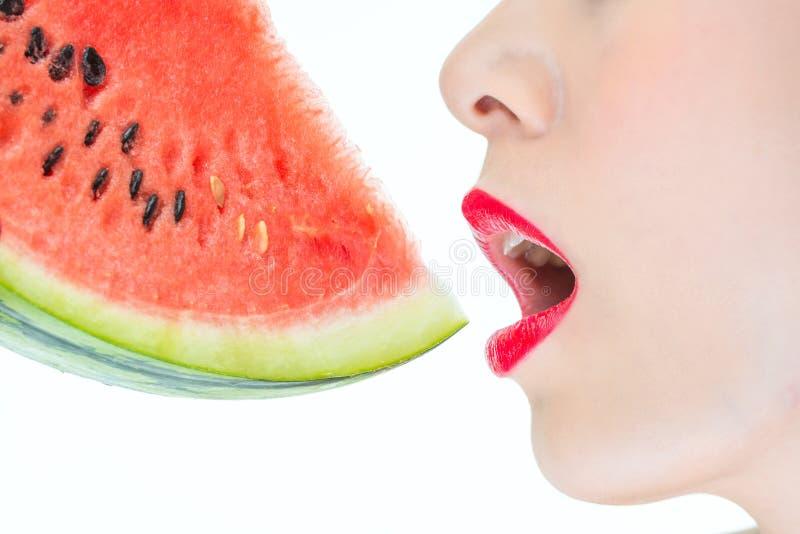 La donna di modo gode di di mangiare le labbra rosse dell'anguria, squisite, il desiderio, T fotografie stock