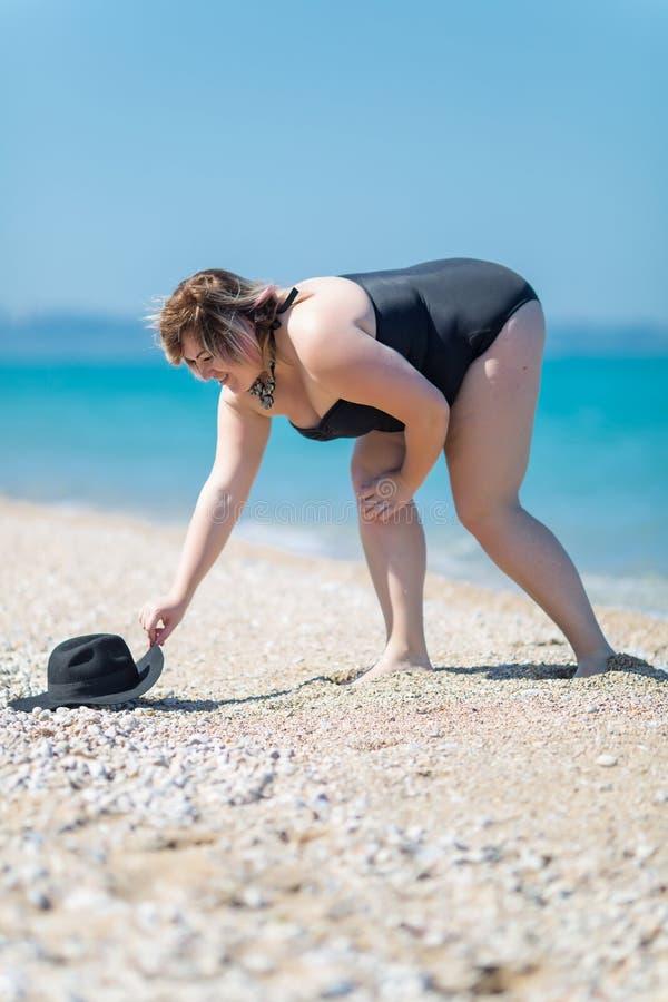 La donna di peso eccessivo in costume da bagno toglie il cappello a terra fotografie stock libere da diritti