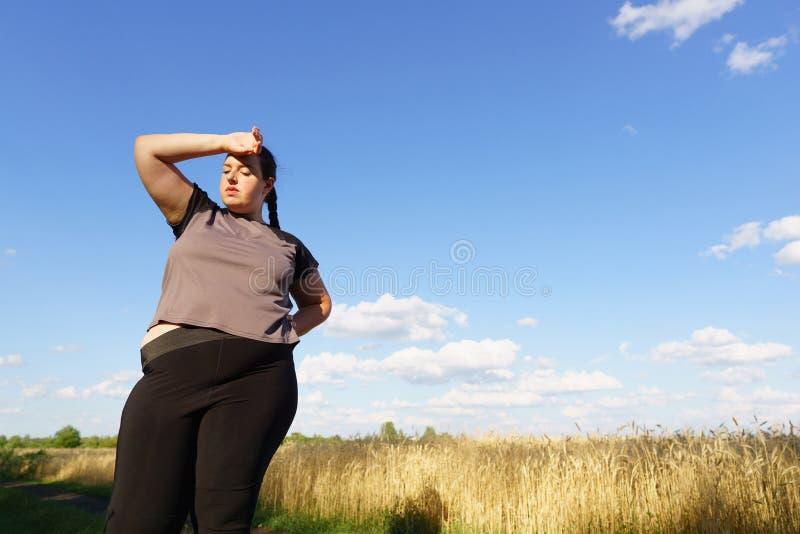 La donna di peso eccessivo ha breve respiro a pareggiare immagini stock