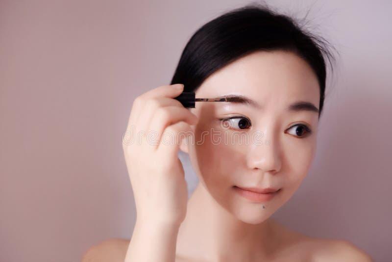 La donna di trucco di bellezza che mette l'occhio della mascara compone fotografie stock libere da diritti