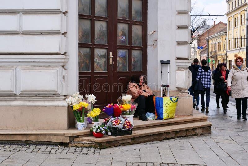 La donna disabile anziana vende i fiori sull'angolo di strada fotografia stock libera da diritti