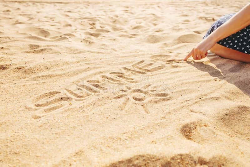 La donna disegna l'estate di parola sulla sabbia fotografia stock