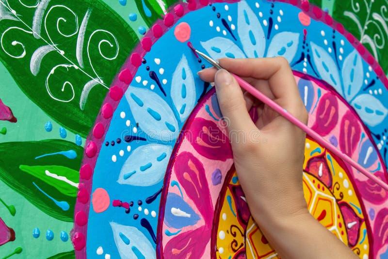 La donna disegna una mandala, mano con un primo piano della spazzola fotografia stock libera da diritti