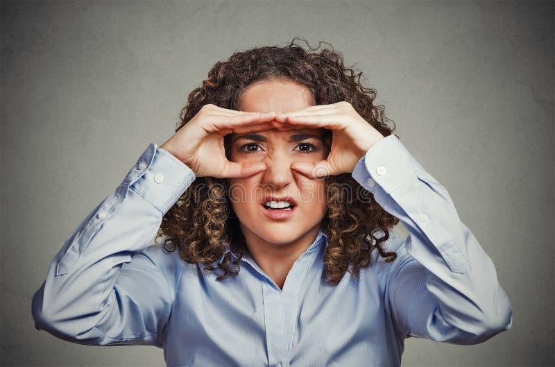 La donna dispiaciuta che guarda tramite le dita gradisce il binocolo fotografie stock libere da diritti