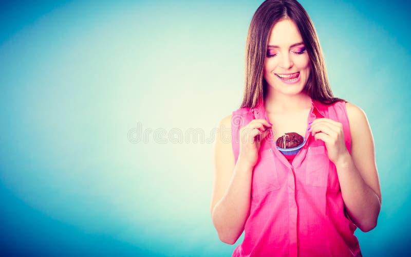 La donna divertente tiene il dolce di cioccolato sul petto fotografia stock