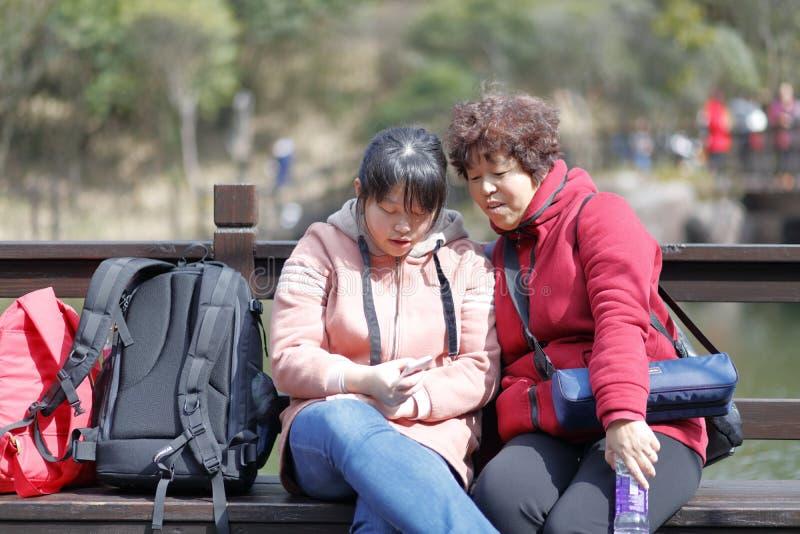La donna e la figlia giocano il telefono dal lago della montagna jiuxianshan, adobe rgb fotografia stock