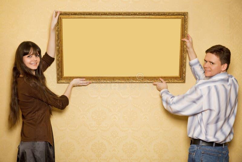 La donna e l'uomo appendono in su sulla maschera della parete fotografie stock libere da diritti