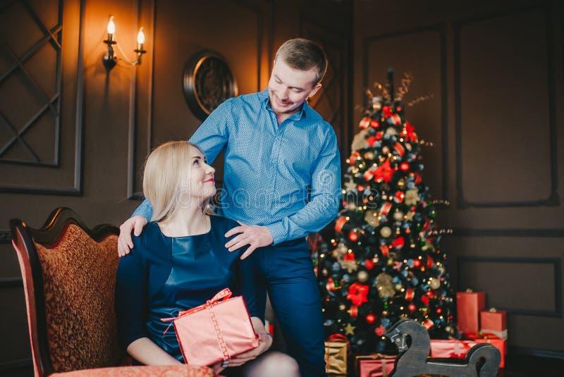 La donna e l'uomo felici con il contenitore di regalo è insieme in salone scuro Se esaminano Vacanza invernale fotografia stock