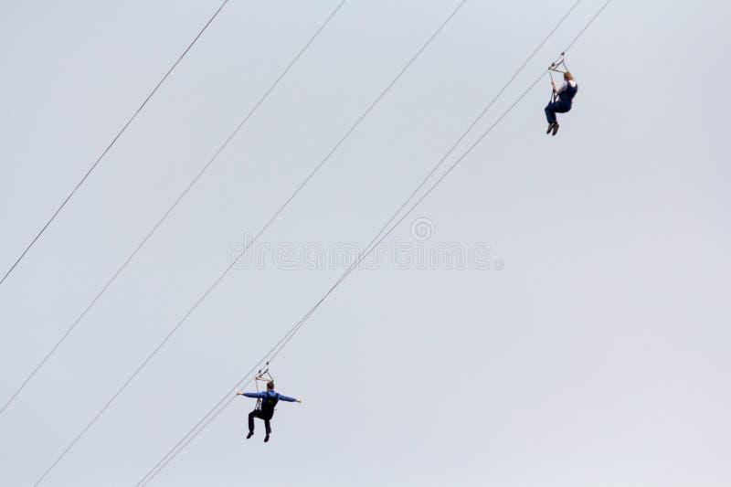La donna e un uomo discendono su una corda contro il cielo sport del reme fotografie stock libere da diritti