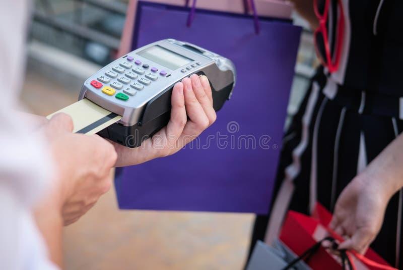 La donna effettua il pagamento con il colpo della carta di credito tramite il terminale Cust immagine stock