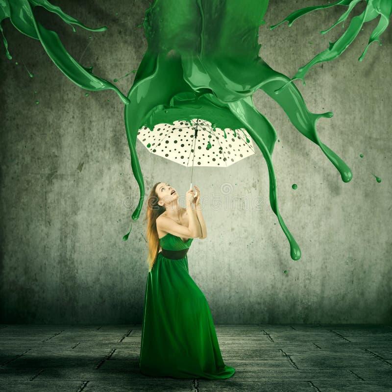 La donna elegante che per mezzo di un ombrello per riparare da colore spruzza la caduta immagini stock