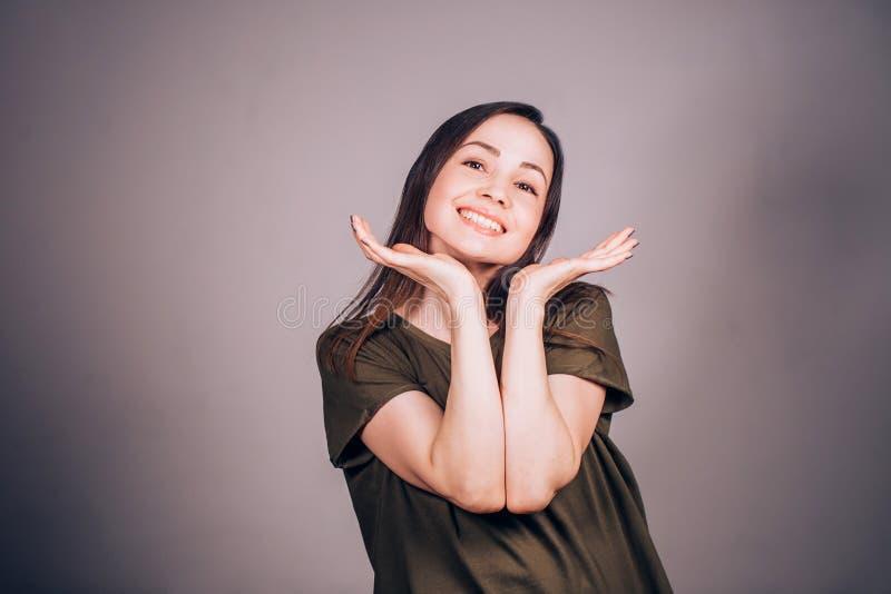 La donna emozionale allegra sorride ed esamina la macchina fotografica, palme sul mento fotografie stock