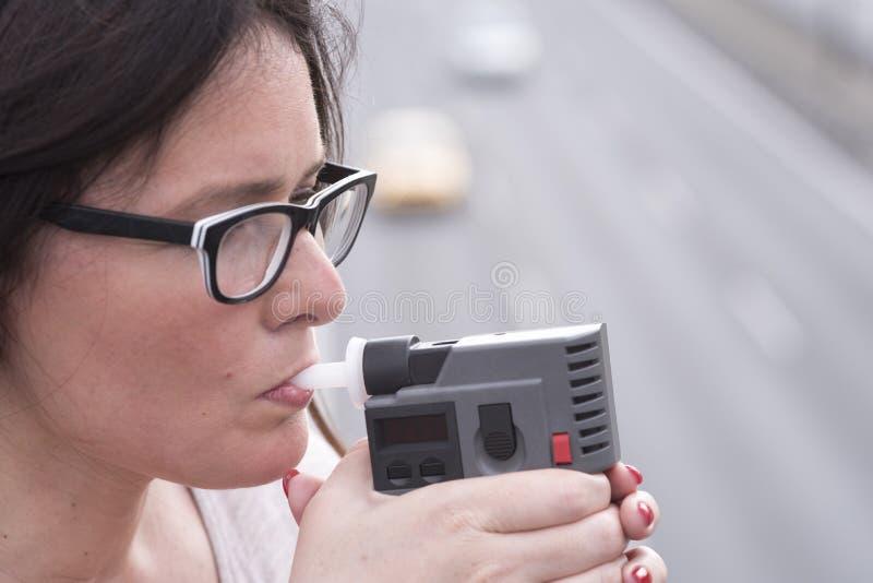 La donna esamina il livello di alcool immagine stock