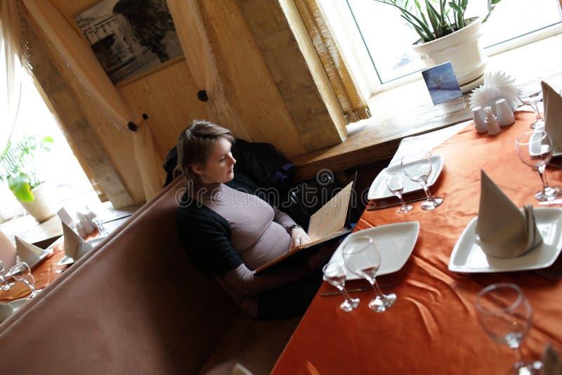La donna esamina il menu fotografia stock