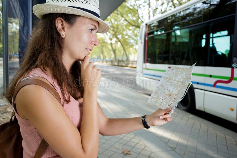 La donna esamina l'itinerario di trasporto pubblico della mappa fotografie stock