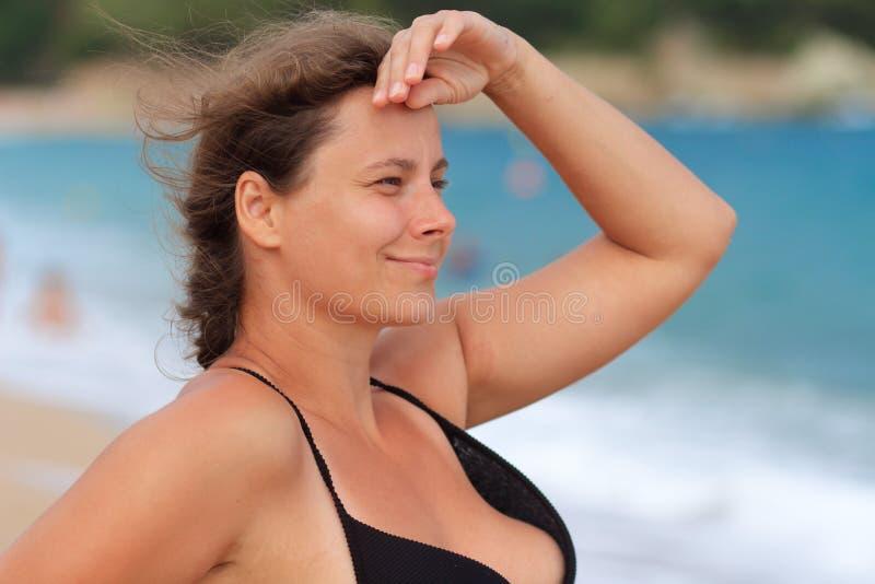 La donna esamina lontano dentro il mare fotografie stock libere da diritti