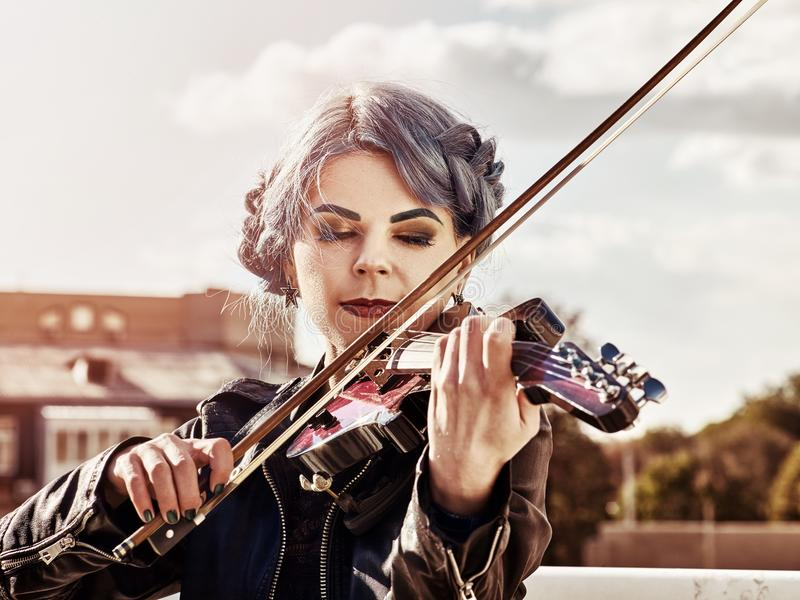 La donna esegue la musica sul parco del violino all'aperto Ragazza che esegue jazz immagine stock libera da diritti