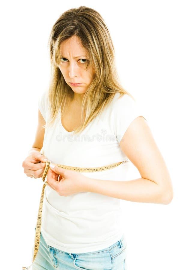 La donna esile bionda in camicia bianca ed i jeans misurano la dimensione del petto con il metro del nastro - non felice fotografia stock