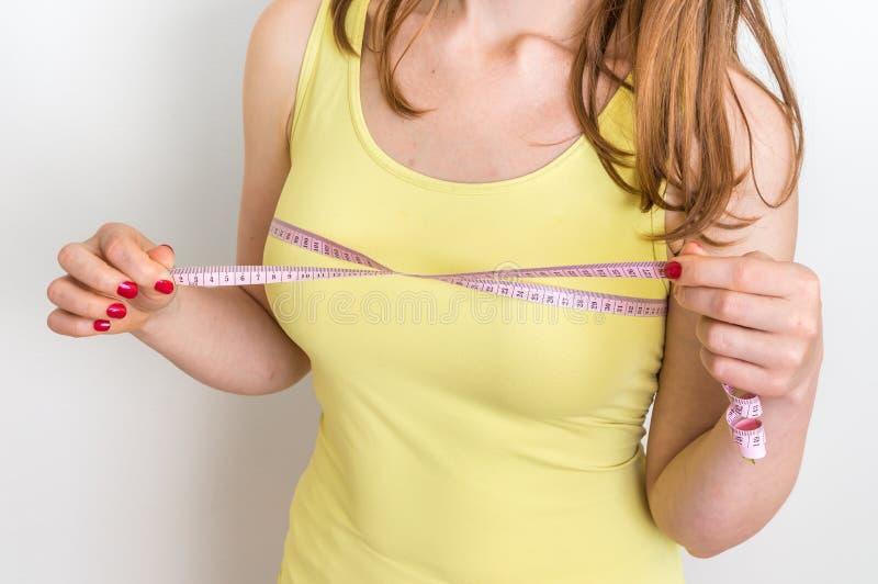 La donna esile misura il suo seno con nastro adesivo di misurazione fotografie stock libere da diritti